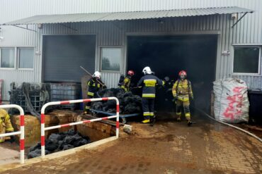 Strażacy gaszą palącą się wełnę stalową ubrani w aparaty ODO