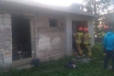 Uszkodzony budynek oraz strażacy biorący udział w akcji