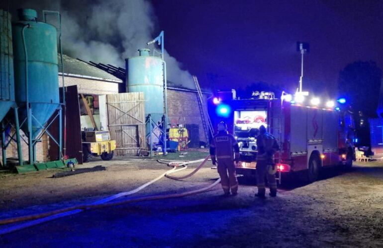 Budynek objęty ogniem oraz samochód pożarniczy