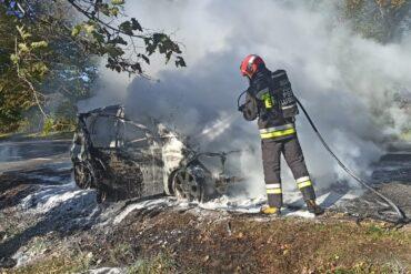 Dym wydobywający się z pojazdu oraz strażak gaszący pożar