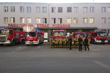 Pojazdy pożarnicze oraz strażacy podczas zbiórki