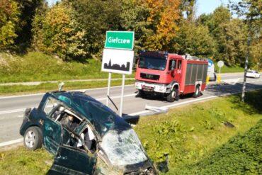 Wrak pojazdu oraz samochód pożarniczy biorący udział w akcji ratunkowej
